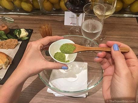 hand spooning macha green tea soup powder into glass bowl at chefs table