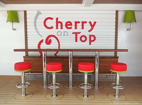 Outdoor dining with red bar stools in front of wall with text Cherry On Top