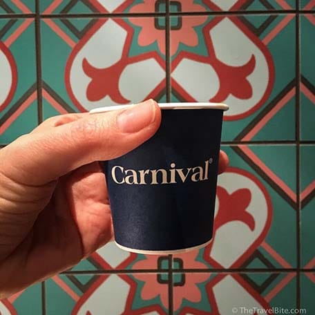 Small to-go cup of Cuban coffee in front of colorful tiled wall