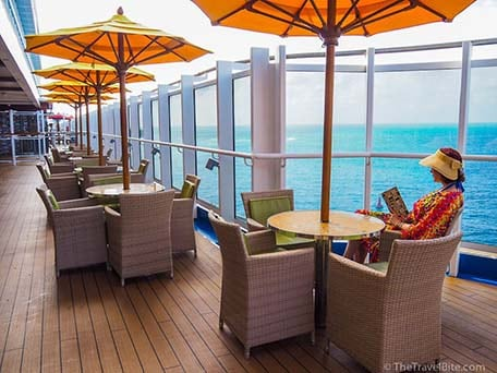 Outdoor round dining tables with yellow umbrellas on the Promenade Deck of carnival ship