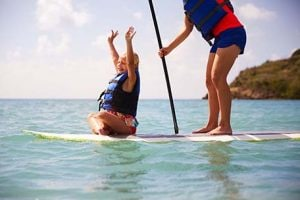 little girl with a big smile and arms up on paddleboard