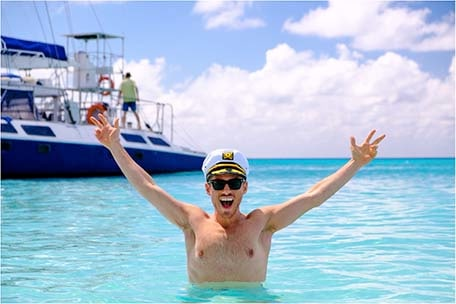 Jeremy in the ocean wearing a captain hat with his arms in the air