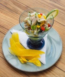 Mint and lime whitefish ceviche served in a clear blue glass