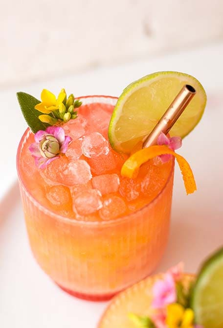 Pineapple mango rum punch cocktail garnished with edible flowers, lime slice and orange zest