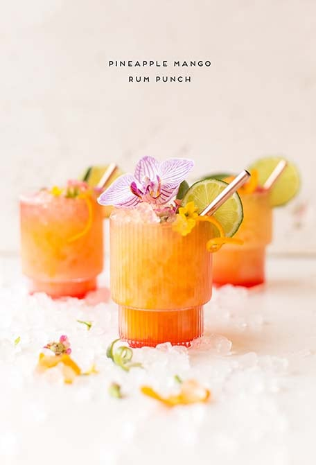 Text overlay of pineapple mango rum punch, with 3 cocktails below