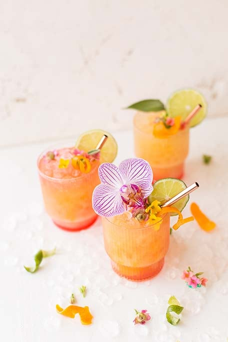 3 pineapple mango rum punch cocktails with flowers sprinkled around on the table