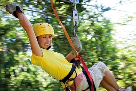 Woman enjoying a zip-line canopy tour