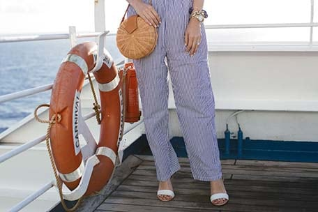 Caroline wearing blue and white stripped pants and carrying a basket bag