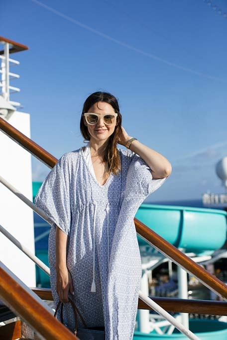Caroline smiling and wearing a caftan and sunglasses