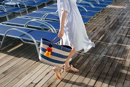 Caroline holding a blue and tan stripped bag with colorful tassels on the pool deck