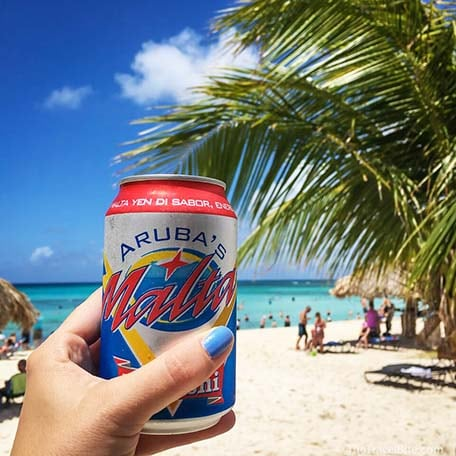 Hand holding a drink in a can with the beach behind