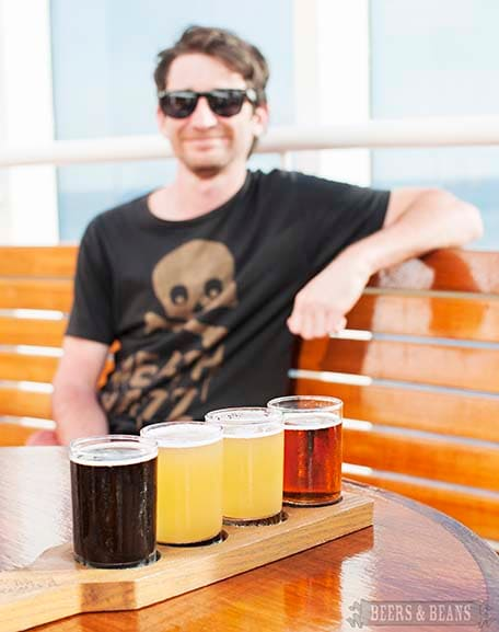 Four beer samples on a wooden holder with Randy in the background