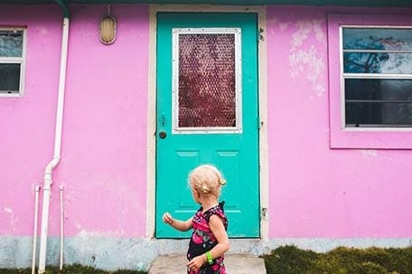 Young girl standing in front of a pink building with green door