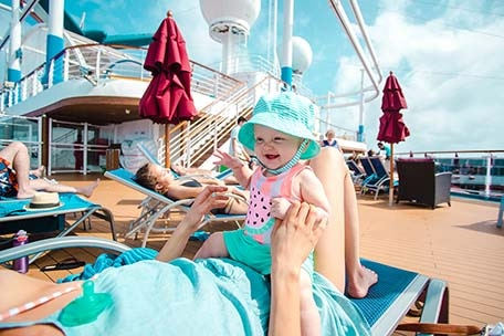 Mother and daughter sitting on a lounge chair on the deck on Carnival Vista