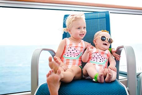Two young girls sitting in a chair and smiling on Carnival Vista