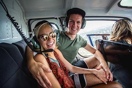 Brad and Hailey smiling while in a helicopter in Grand Cayman