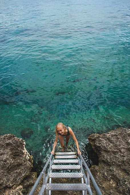 Hailey going down a ladder into the ocean