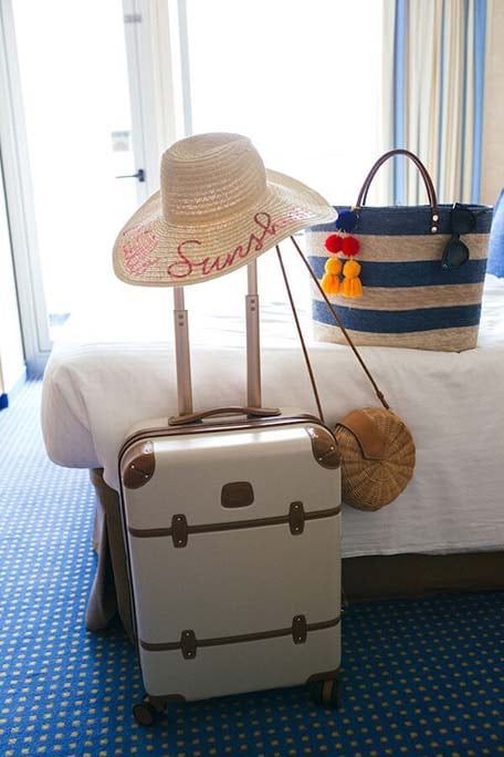 Suitcase, beach bag and sun hat inside a balcony stateroom on the Carnival Victory