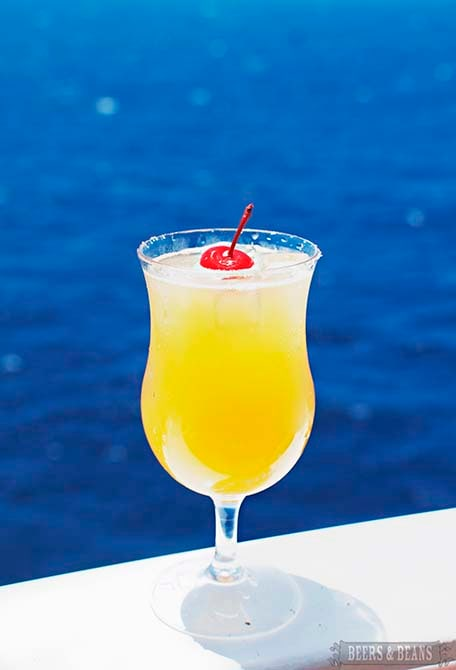 Orange drink with red cherry on top with bright blue ocean behind