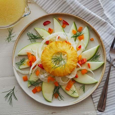 Overhead view of grilled pineapple and fennel salad plated on a table with a fork and dressing on the side