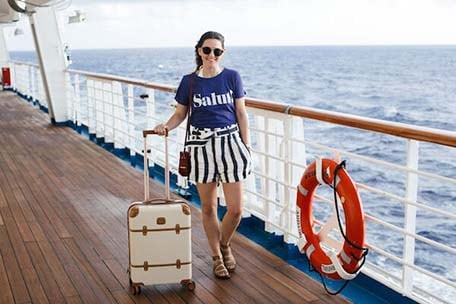 Caroline posing on the Carnival Victory deck with her suitcase next to her