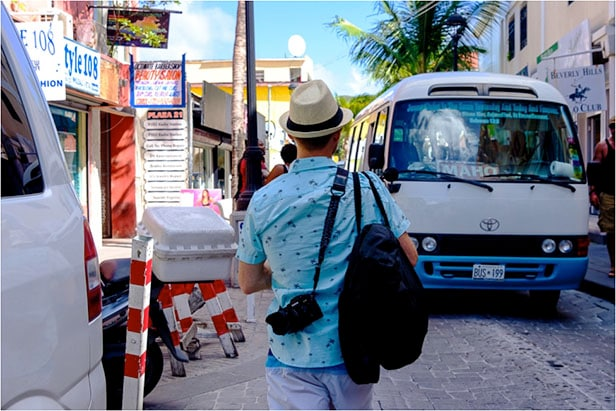 Jeremy wearing a hat and carrying his bag and camera while walking around St. Maarten