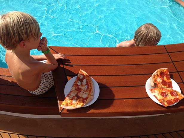 children swimming and eating pizza by the pool