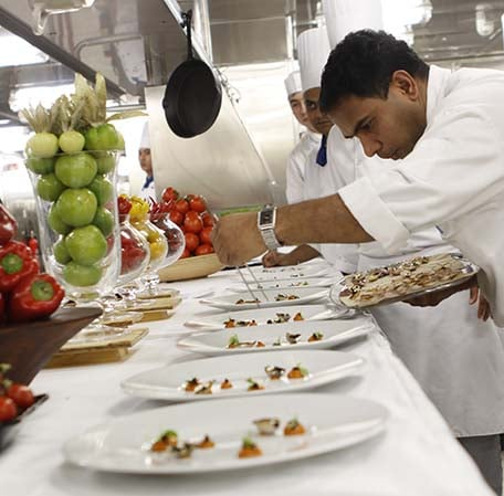 chef prepares dishes for the multi-course dinner