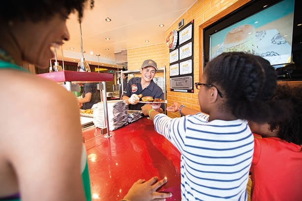 chef serving hamburger to customer at guy's burger joint