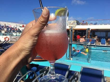 Hand holding up a pink margarita with a pool behind on the Carnival Conquest