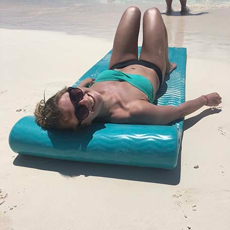 Sarah laying on a beach float on the beach