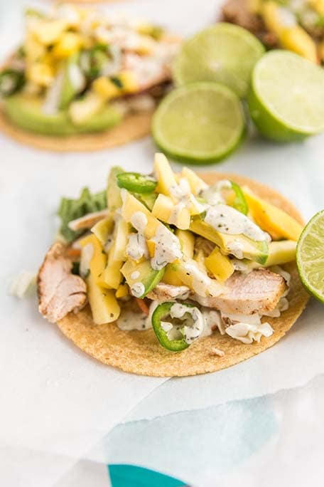 Close up of pineapple mango chicken taco with a few limes in the background