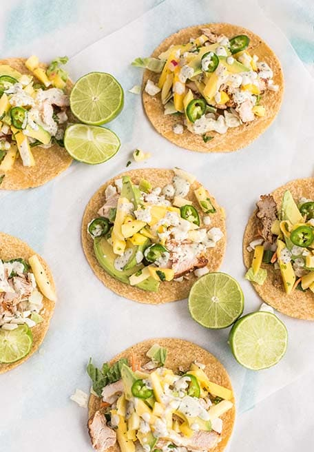 Overhead image of pineapple mango chicken tacos with limes on a table