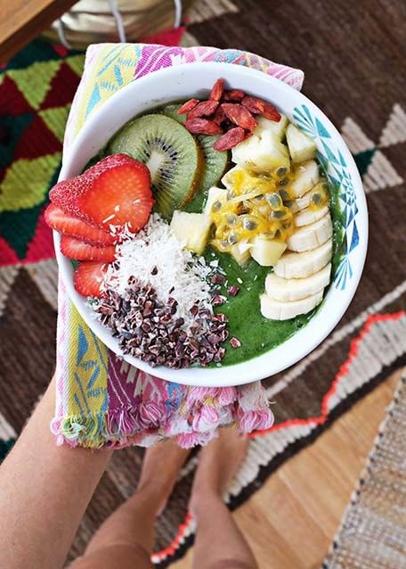 Hand holding out a green smoothie bowl with many fruit toppings
