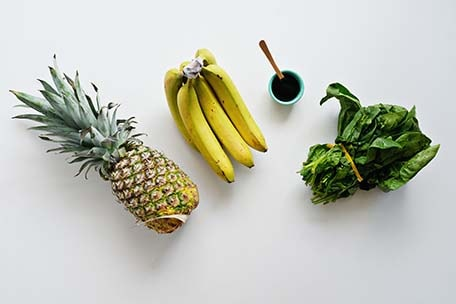 Overhead image of pineapple, bananas and greens on white table