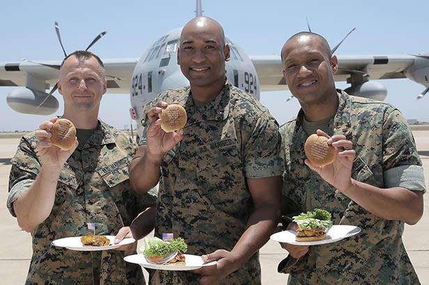three marines show off the messages lasered onto their burger buns