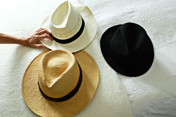 3 hats sitting on top of a bed with a hand reaching out to grab one