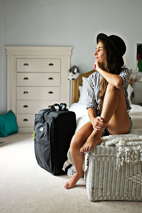 Andrea sitting on a bed and wearing a hat with a suitcase next to her