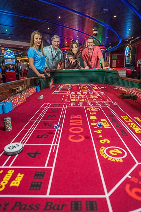 guests playing a game of craps at the onboard casino