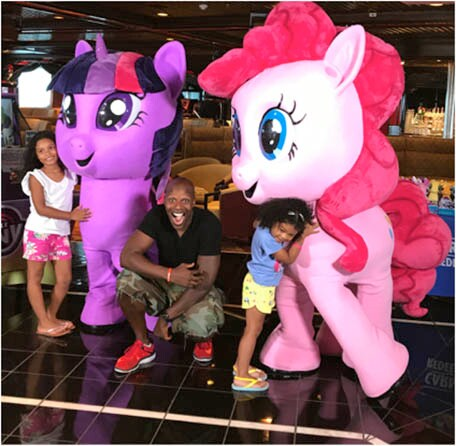 Doyin and his two daughters posing with My Little Pony friends