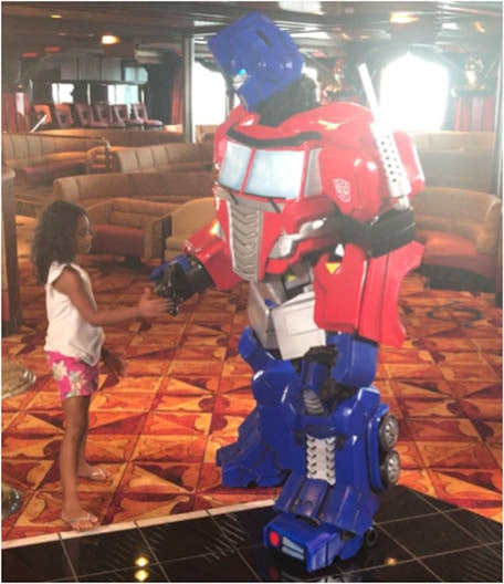 One of Doyin's daughters shaking hands with a Transformer on Carnival Imagination