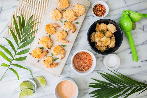 Overhead photo of coconut shrimp and ingredients on a kitchen counter