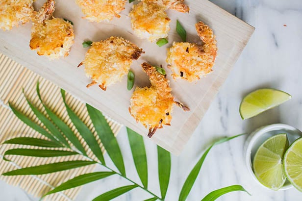 Breaded coconut shrimp laying on a baking pan