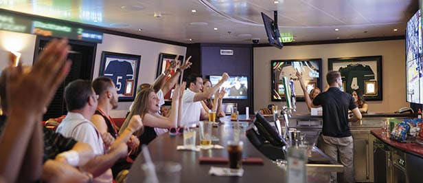 a group of people enjoying drinks while watching a sports game