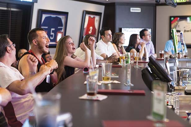 : fans cheering on their teams in the sports bar