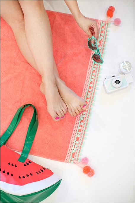 Feet resting on DIY pompom beach towel