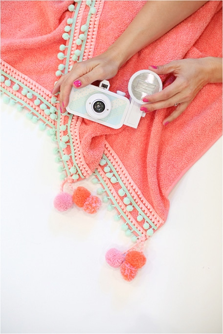 Hands holding a camera on top of DIY pompom beach towel
