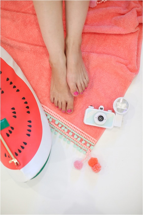 Feet and camera sitting on top of DIY pompom beach towel