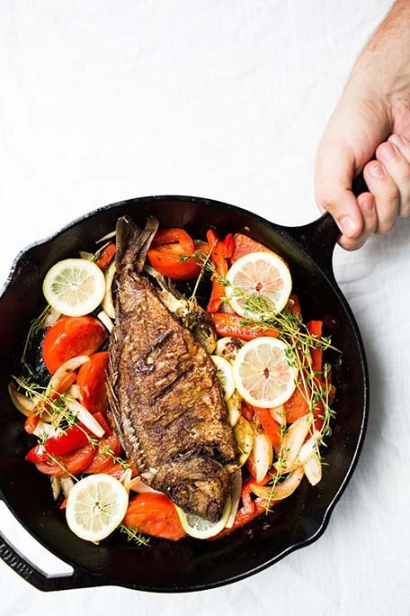 Hand holding out cast iron pan with grilled fish and cooked vegetables