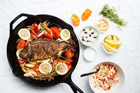 Overhead photo of Caribbean style grilled fish in a pan with ingredients on the side